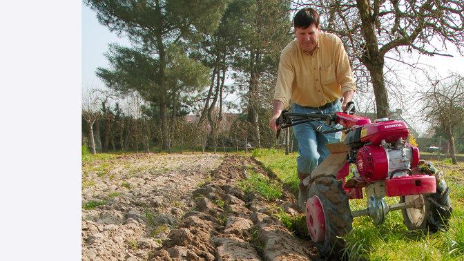 Motoculteur transformable utilisé par un démonstrateur dans un jardin.