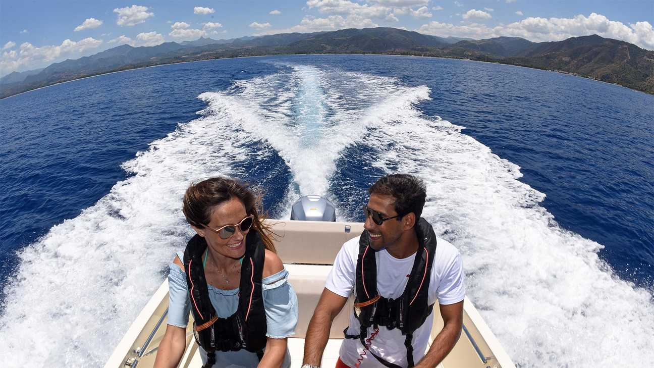 Young couple enjoying a ride on a Honda speedboat, in coastal location.